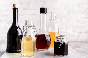 original glass bottles with different vinegar on a marble table against a table of a white brick wall copy space horizontal - Жареный корень лопуха