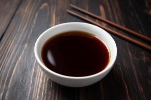 soy sauce and soy bean on wooden table - Жареный корень лопуха