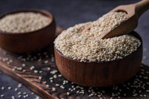 white sesame in a wooden spoon on dark table sesame oil in jar and seeds - Жареный корень лопуха